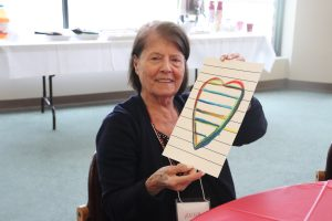 A care partner holding up her heart painting